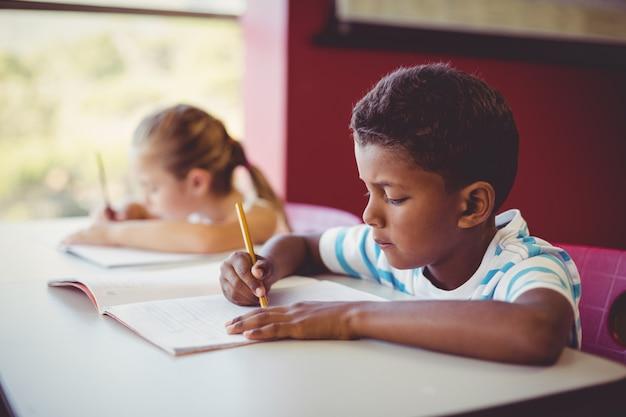 Crianças da escola fazendo lição de casa em sala de aula