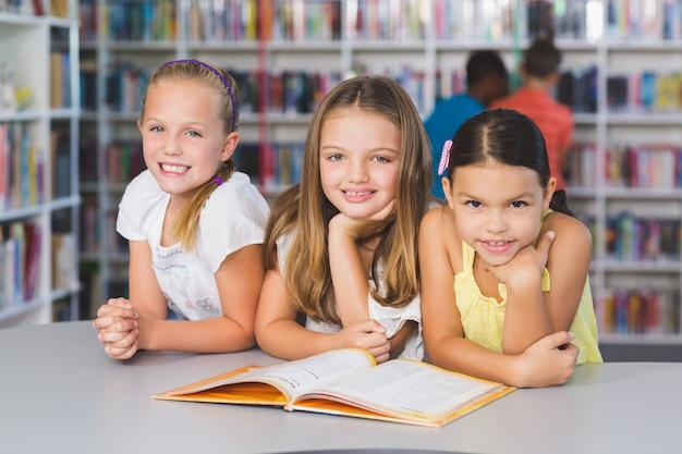 Crianças da escola lendo livro juntos na biblioteca