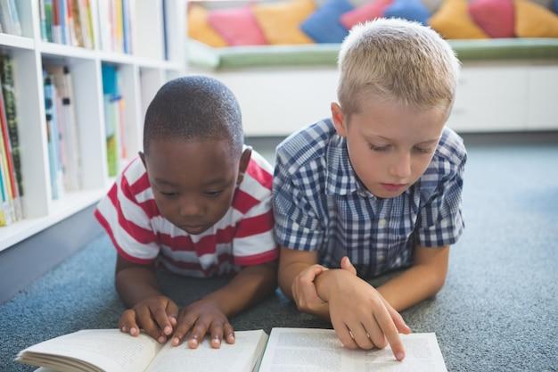 Crianças da escola lendo livro na biblioteca