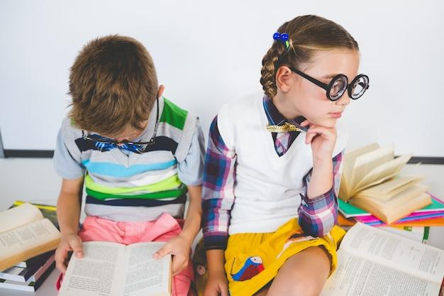 Crianças da escola lendo livro na sala de aula
