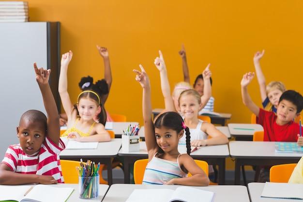 Crianças da escola levantando a mão na sala de aula