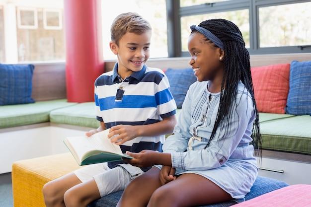 Crianças da escola sentados juntos no sofá e lendo o livro