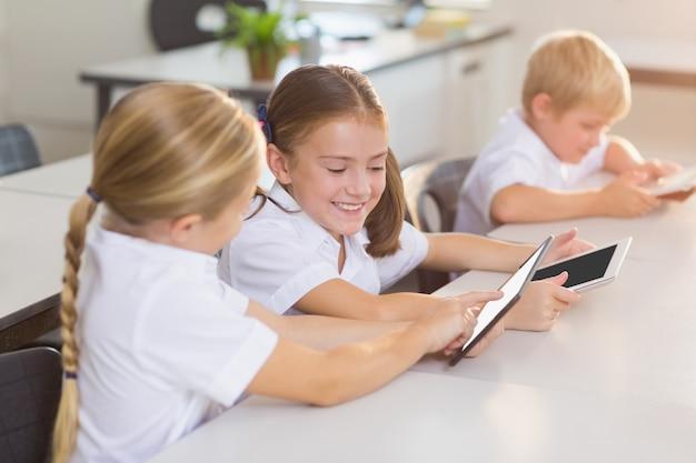 Crianças da escola usando tablet digital em sala de aula
