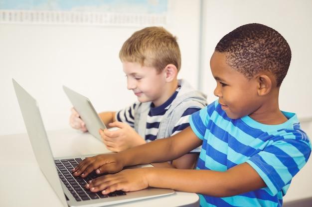 Crianças da escola usando um laptop e tablet digital em sala de aula