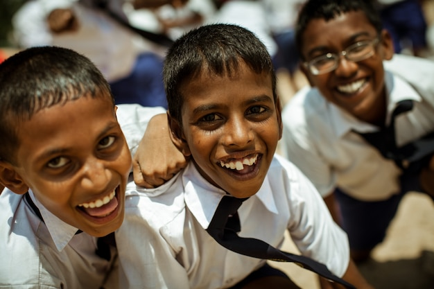 Crianças da escola vestidas de uniforme se divertem e brincam no pátio da escola.