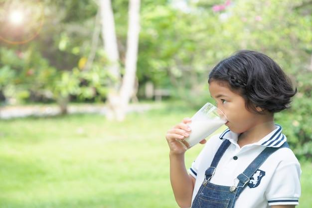 Crianças da menina que bebem o leite no parque para o café da manhã.