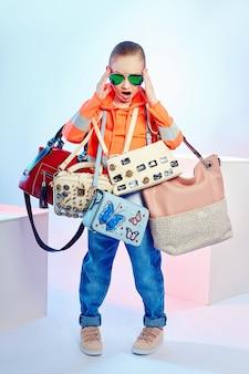 Crianças da moda posam com uma coleção de bolsas e embreagens.