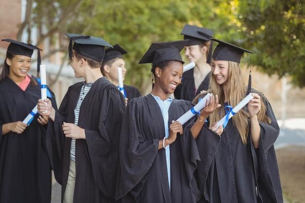 Crianças da pós-graduação em pé com a rolagem de diplomas no campus na escola