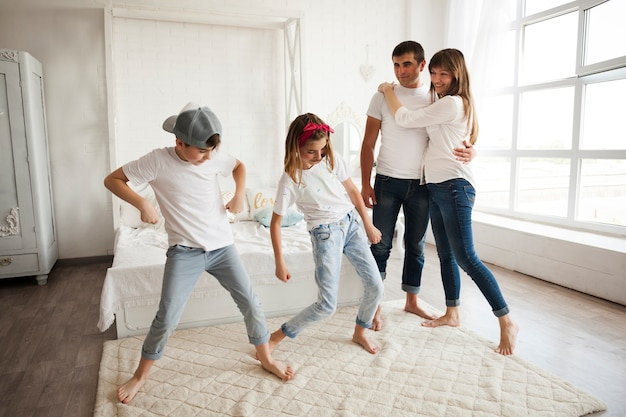 Crianças dançando na frente de seus pais amorosos em casa