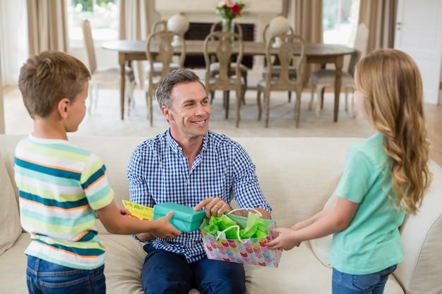 Crianças dando presente surpresa para seu pai