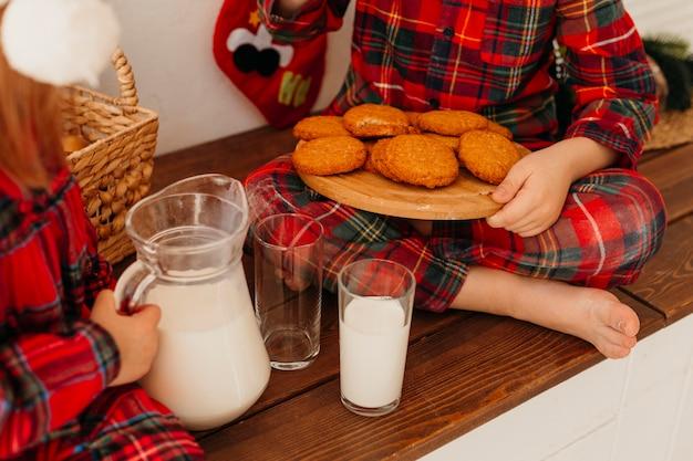 Crianças de alto ângulo comendo biscoitos de natal e bebendo leite