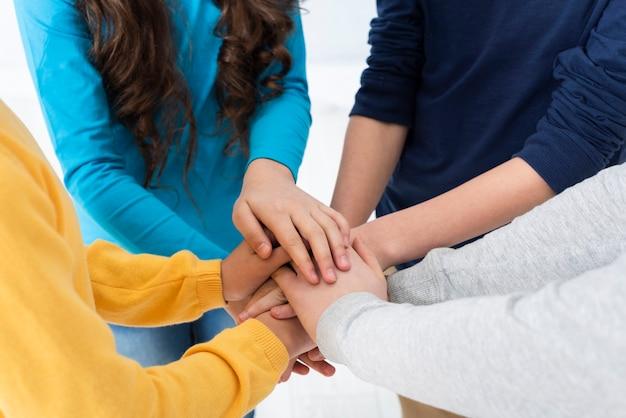 Crianças de alto ângulo, formando pilha de mãos