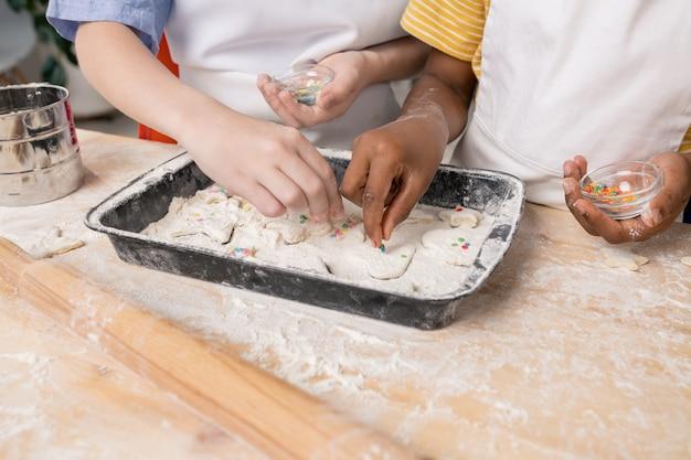 Crianças de avental branco cortando bonecos na massa enrolada enquanto fazem biscoitos saborosos para o feriado