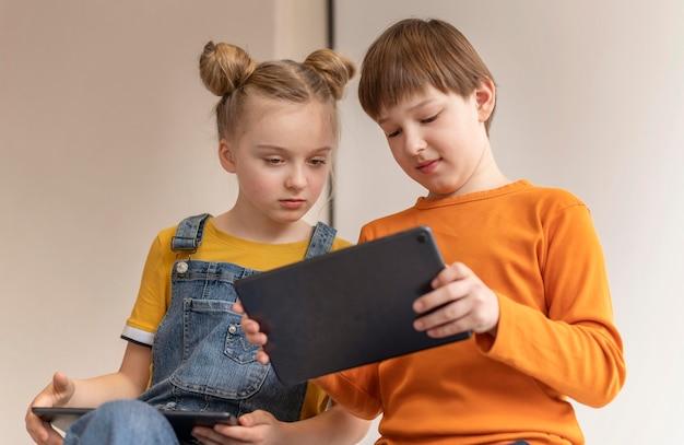 Crianças de baixo ângulo aprendendo com dispositivos