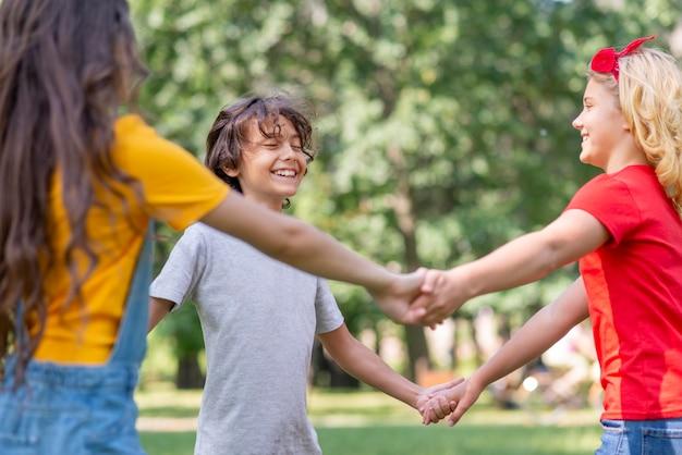 Crianças de baixo ângulo, de mãos dadas