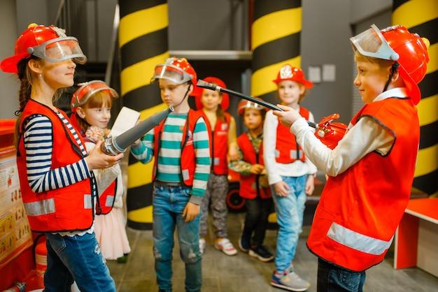 Crianças de capacete e uniforme com mangueira e extintor nas mãos brincando de bombeiro