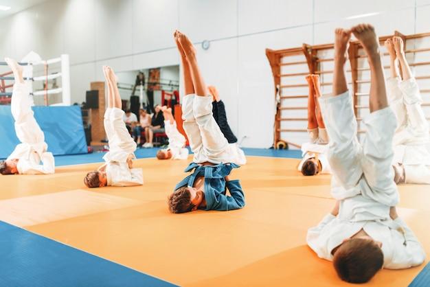 Crianças de caratê, crianças de quimono praticam arte marcial no ginásio. meninos e meninas uniformizados fazem exercícios de cabeça para baixo no treinamento esportivo