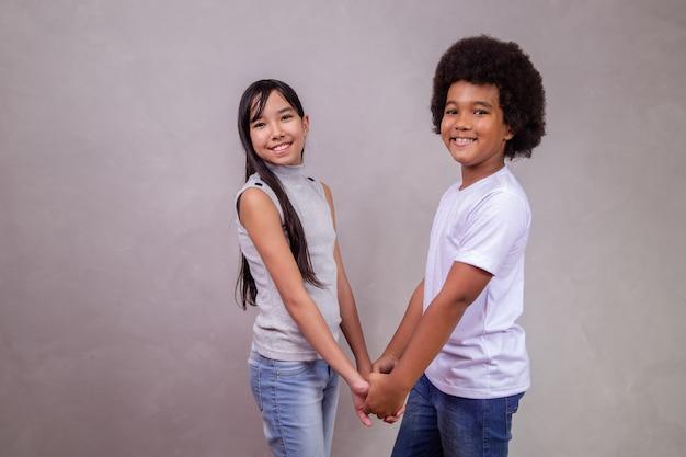 Crianças de diferentes diversidades em fundo cinza. menina japonesa com uma criança afro em fundo cinza com espaço para texto.