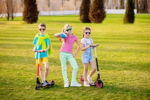 Crianças de esportes com um skate no parque na primavera. esportes ao ar livre.