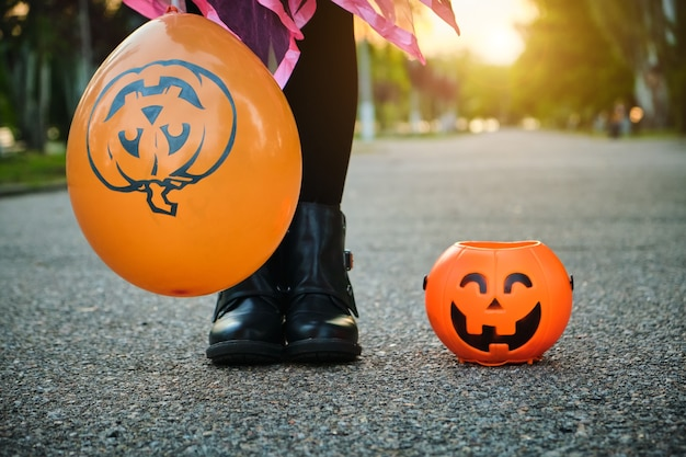 Crianças de halloween. close-up dos pés de uma criança com balde de bala de abóbora.
