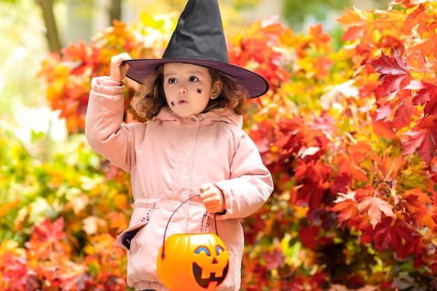 Crianças de halloween no outono. engraçada linda garota de chapéu preto, abóbora jack, balde doce doce no outono.