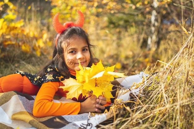 Crianças de halloween. retrato de uma menina sorridente com cabelo castanho e chapéu de bruxa deitada no solo de outono