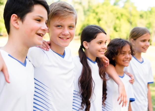 Crianças de lado em roupas esportivas abraçadas