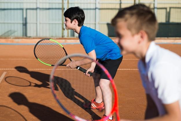 Crianças de lado jogando tênis de duplas