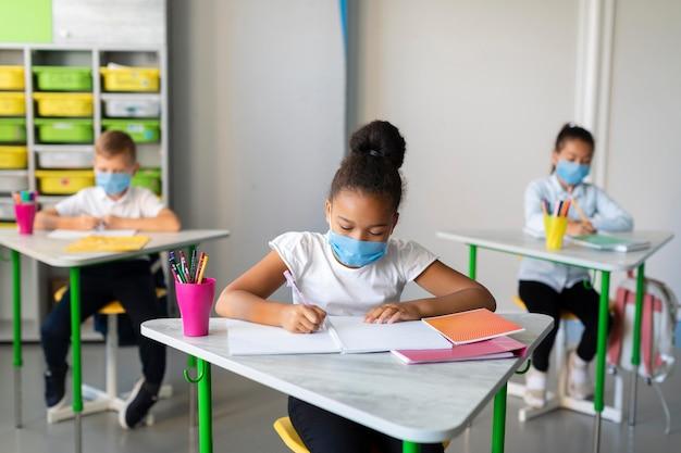 Crianças de longa data se protegendo com máscaras médicas