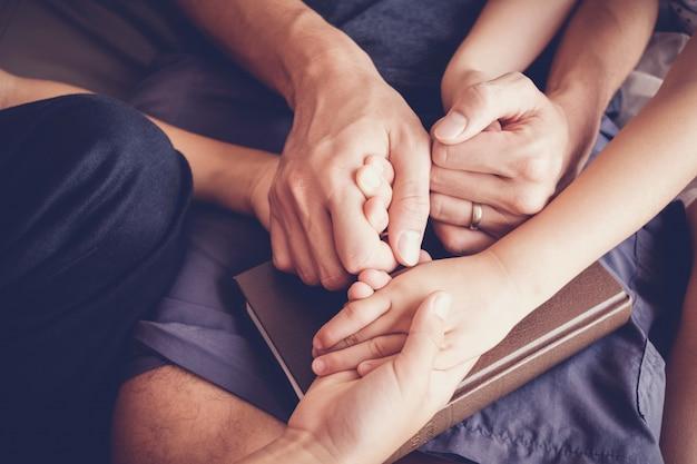 Crianças de mãos dadas e rezando com seus pais em casa, a família reza, ter fé e esperança.