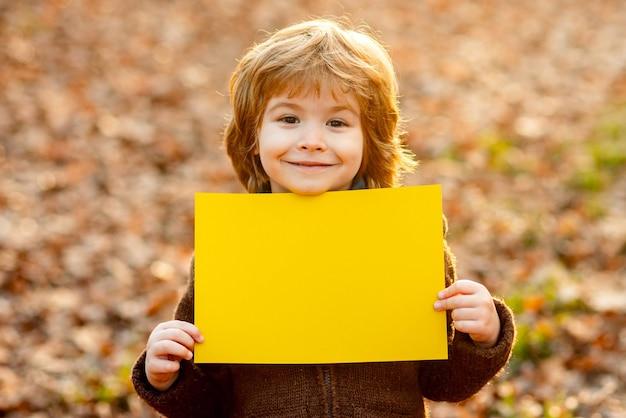 Crianças de outono anunciando criança sorridente segurando uma folha em branco para crianças de publicidade e venda de espaço de texto ...