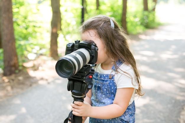 Crianças de profissão de passatempo e criança do conceito de fotógrafo com câmera na floresta