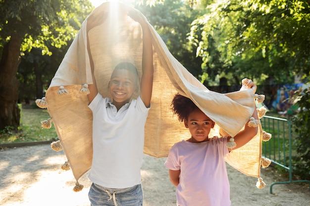Crianças de tiro médio brincando com cobertor