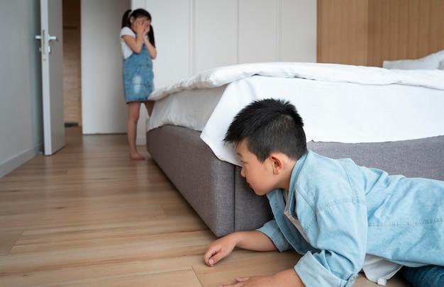 Crianças de tiro médio brincando de esconde-esconde