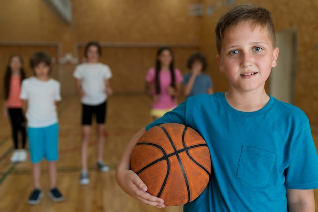Crianças de tiro médio com bola de basquete na academia