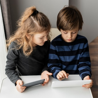 Crianças de tiro médio com dispositivos