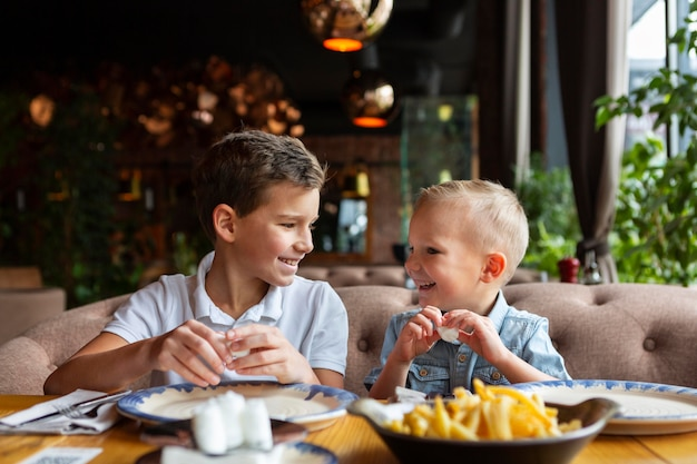 Crianças de tiro médio comendo fast food