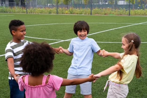 Crianças de tiro médio de mãos dadas