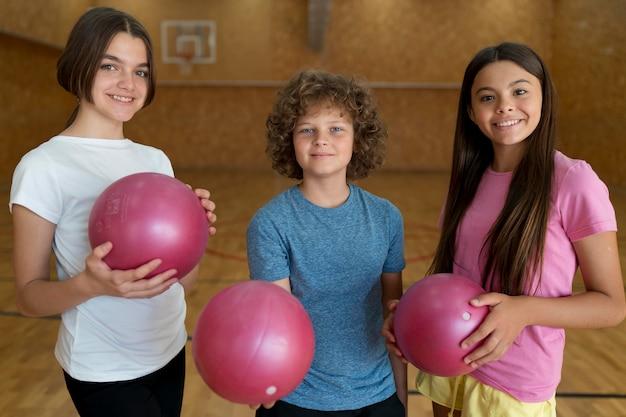 Crianças de tiro médio segurando bolas