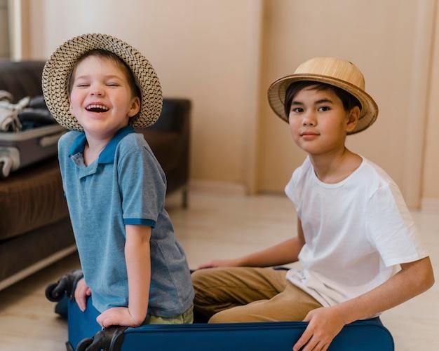Crianças de tiro médio sentadas na bagagem