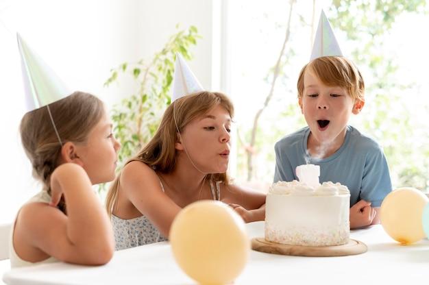 Crianças de tiro médio soprando velas