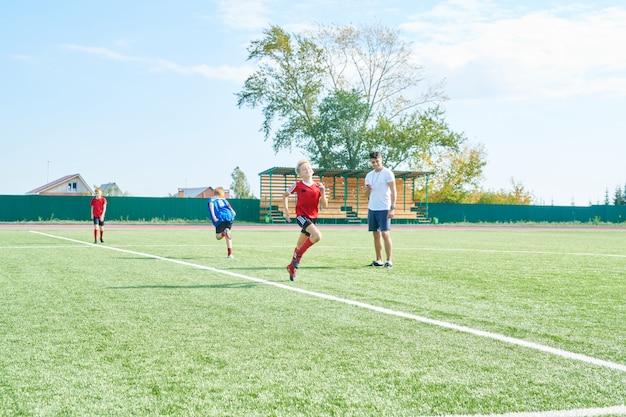 Crianças de treinamento de treinador de futebol