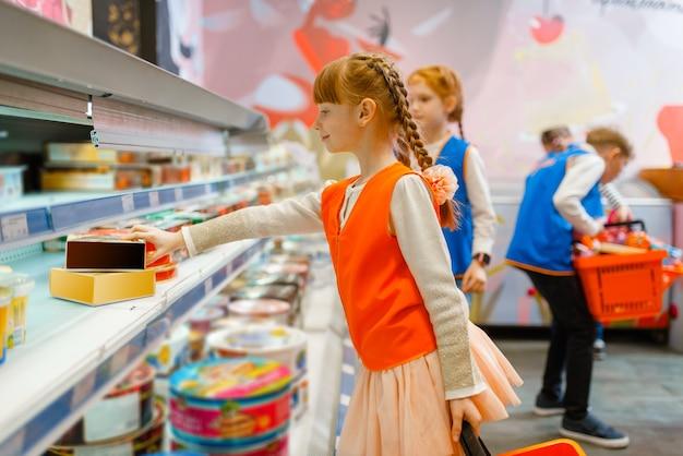 Crianças de uniforme brincando de vendedoras, sala de jogos. k