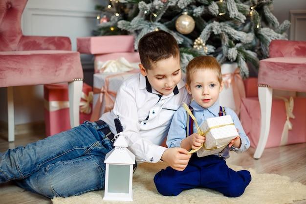 Crianças debaixo da árvore de natal com caixas de presente. sala decorada