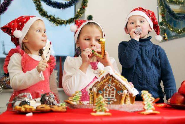 Crianças decorando casa de pão de gengibre