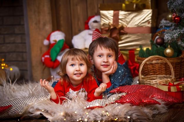 Crianças deitadas na pele com um chapéu de papai noel ao lado da árvore de natal