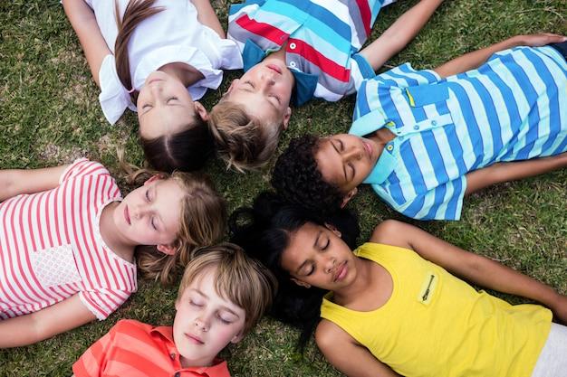 Crianças, deitado na grama com os olhos fechados
