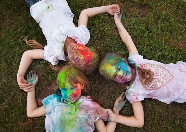 Crianças deitam-se na grama. crianças pintadas com as cores do festival holi deitam-se na grama.
