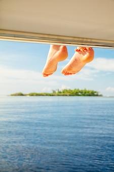 Crianças descalças no convés do barco com uma pequena ilha e mar azul
