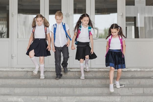 Crianças descendo os degraus da escola